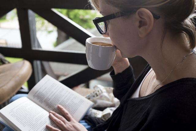 コーヒーを飲みながら読書をする女性