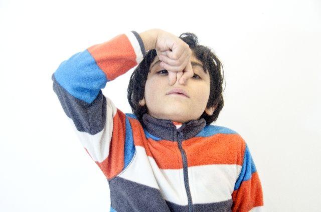 鼻をつまむ少年